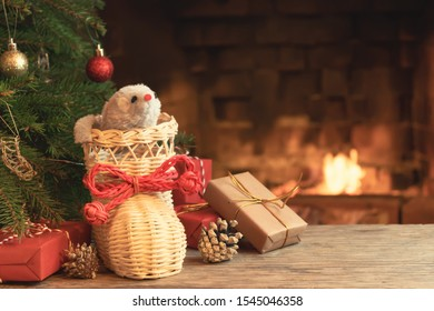Christmas composition - mouse is symbol of 2020 according to Chinese horoscope in wicker boot under Christmas tree in room by fireplace