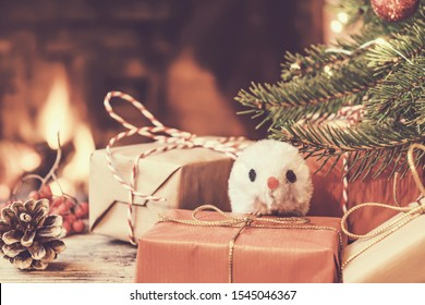 Christmas composition - mouse is symbol of 2020 according to Chinese horoscope next to gifts under Christmas tree in room by fireplace