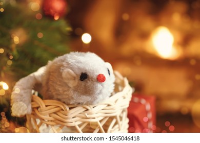 Christmas composition - mouse is symbol of 2020 according to Chinese horoscope in wicker boot near Christmas tree in room by fireplace