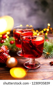Christmas composition with mulled wine with its ingredients & spices on wooden textured table. Traditional drink on winter holiday season. Copy space, close up, top view, background.