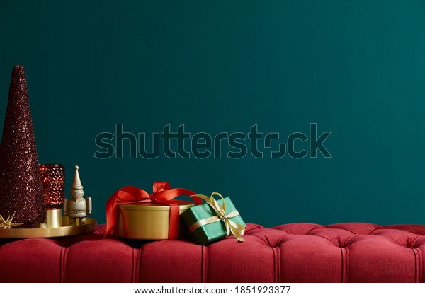 Christmas composition on the red velvet bench with decoration, gifts, wreath, lantern and accessories. Copy space. Red and green color. Template.