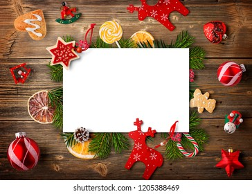 Christmas composition. Paper blank, christmas tree branches and decorations on wooden background. Flat lay, top view, copy space