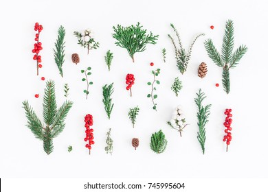 Christmas composition. Pattern made of christmas tree branches and red berries on white background. Flat lay, top view