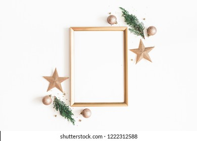 Christmas composition. Photo frame, golden decorations, fir tree branches on white background. Christmas, winter, new year concept. Flat lay, top view, copy space