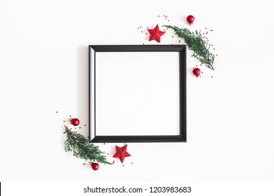 Christmas composition. Photo frame, red decorations, fir tree branches on white background. Christmas, winter, new year concept. Flat lay, top view, copy space