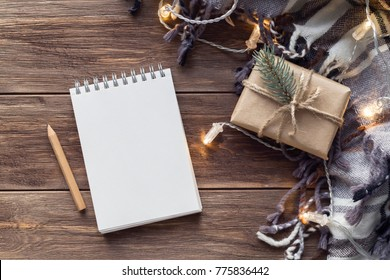 Christmas composition with plaid, lights, gift in craft paper and notebook on the wooden background. Flat lay, top view, copy space, mock up
