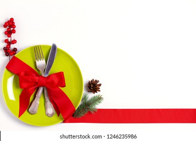 Christmas composition with plate, cutlery, pine branches, ribbon and red berries on white table. Winter holidays and festive background. Christmas eve dinner, New Year food lunch. View from above, top