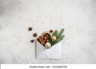 Christmas composition with spices, fir branch, ornaments and envelop, flat lay on white, copy space. Christmas greeting card, desigh, concept.