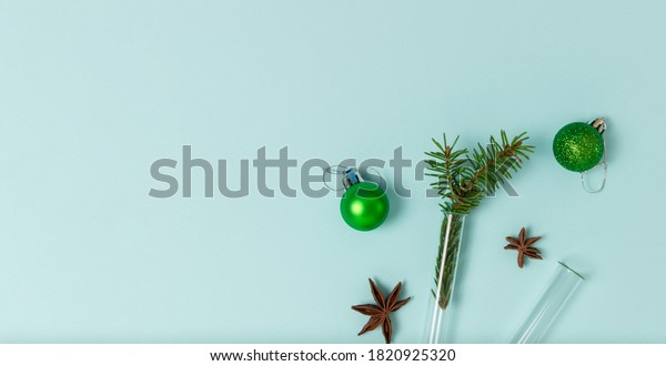 Christmas composition of test tubes, festive balls, cinnamon and star anise on a mint background with copy space. Top view, flat lay. Medical New Year concept