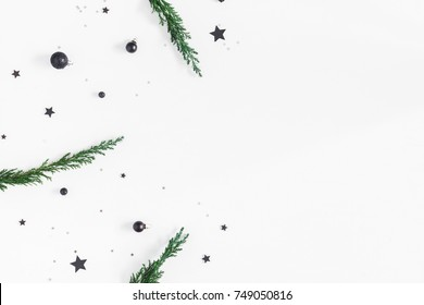 Christmas composition. Christmas tree branches and black decorations on white background. Flat lay, top view, copy space
