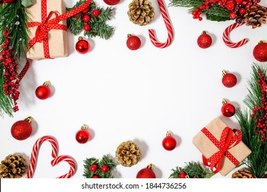 Christmas composition with Christmas tree decorations on a white background with red decor, lollipops and gifts. Frame for text. Isolate. Layout. Flat lay, top view, copy space, still life, background