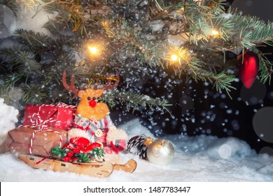 Christmas composition - Christmas tree in the snow, gifts, toy deer and the inscription Merry Christmas and Happy New Year, copy space, place for text