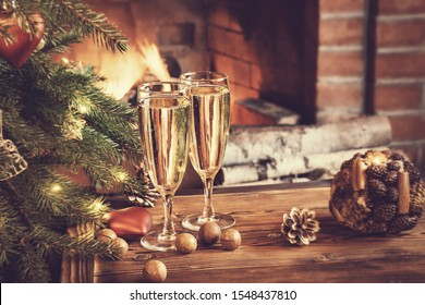 Christmas composition - Two glasses with champagne on a wooden table near a Christmas tree in a room with a burning fireplace.