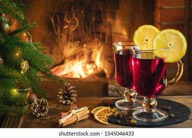 Christmas composition - two glasses with mulled wine on a wooden table near a Christmas tree opposite a burning fireplace