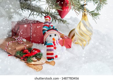Christmas composition under the Christmas tree - a snowman, boxes with gifts on a sled and other decorations, place for text, copy space