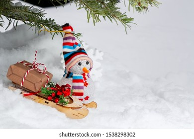 Christmas composition under the Christmas tree - a snowman, boxes with gifts on a sled, place for text, copy space
