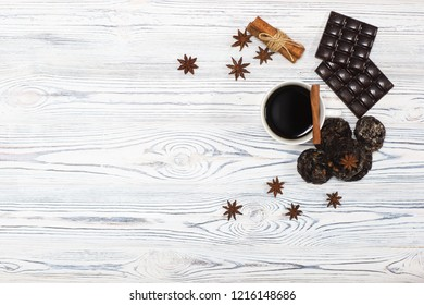 Christmas composition. White cup with black coffee, black chocolate, cinnamon sticks, biscuits on a wooden gray white background. Winter, new year, christmas concept. Flat lay for blogers.