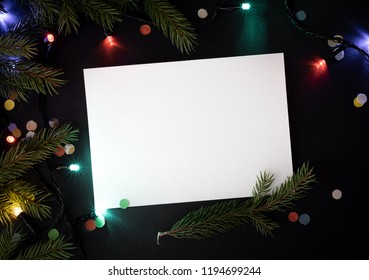 Christmas composition with white paper sheet for festive text. New Year decor with fir branch and garland. New Year concept. Flat lay, top view, copy space