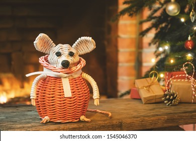 Christmas composition - a wicker white mouse - symbol of 2020 according to Chinese horoscope next to gifts under Christmas tree in room by fireplace.