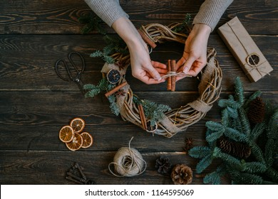 Christmas composition. Woman making handmade christmas wreath on dark wooden rustic table. The concept of preparation for the happy holidays. Festive interior decor. Top view, flat lay with copy spase