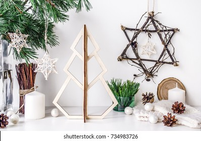 Christmas composition with a wooden stylish Christmas tree on the background of different New Year's accessories.