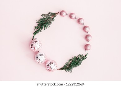 Christmas composition. Wreath made of fir tree branches, pink balls on pastel pink background. Christmas, winter, new year concept. Flat lay, top view, copy space