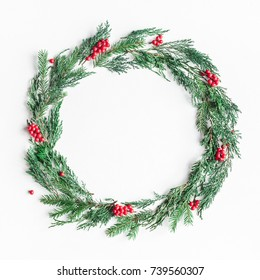 Christmas composition. Wreath made of christmas tree branches and red berries on white background. Flat lay, top view, copy space, square