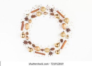 Christmas composition. Christmas wreath, pine cones, golden decorations, cinnamon stick, anise stars on white background. Flat lay, top view, copy space