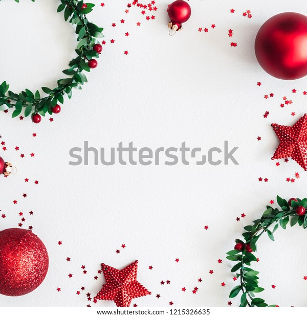 Christmas composition. Wreaths, red decorations on pastel gray background. Christmas, winter, new year concept. Flat lay, top view, copy space, square