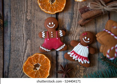 Christmas composition. Xmas cookies, Gingerbread man, tangerines, cinnamon, festive decoration, fir branches on dark old wooden background. Flat lay, top view, with copy space.