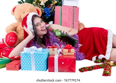 Christmas concept : Beautiful smiling young Asian woman in Santa Claus costume holding bottle of red wine with Christmas tree and Christmas gifts isolated on white background