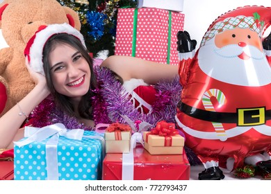 Christmas concept : Beautiful smiling young Asian woman in Santa Claus costume with Christmas tree and Christmas gifts