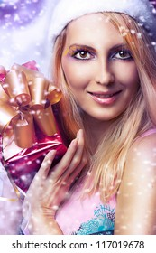 Christmas concept. Beauty portrait happy woman model holding gift in hands and smile in santa claus hat and with bright make-up