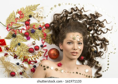 christmas concept close-up portrait of cute curly brunette woman surrounded by colorful xmas decorations, red baubles, golden branch, ribbon and stars on her face.