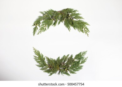 Christmas concept - frame wreath with evergreen Cupressus nootkatensis leaves. Flat lay, top view.