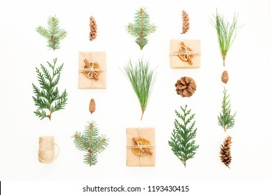 Christmas concept with gift boxes, winter plants and pine cones on white background. New year composition. Flat lay. Top view
