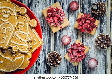 Christmas concept with gingerbread, gifts and snow. Sweet gingerbreads, gifts and baubles on a wooden table.