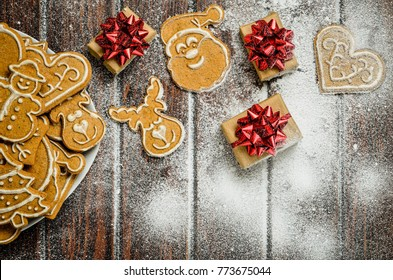 Christmas concept with gingerbread, gifts and snow. Sweet gingerbreads and gifts on a wooden table.