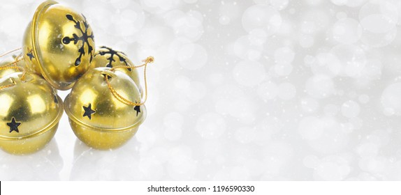 Christmas Concept: Gold Jingle bells on a snowy bokeh silver background with copy space.