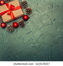 Christmas concept, greeting card, gift box, Christmas toys and cones, on a gray background, space for text flat lay