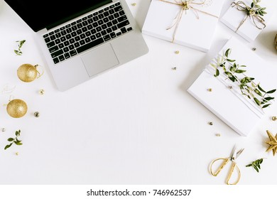 Christmas concept. Laptop and handmade Christmas gift boxes on white table desk. Flat lay, top view holiday composition.