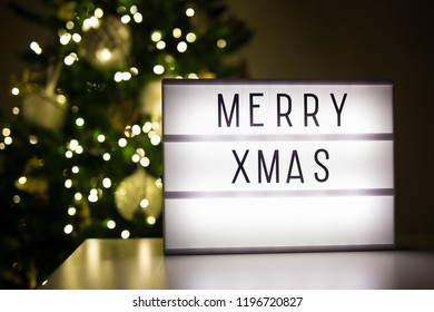 christmas concept - lihtbox with merry xmas words in dark room with decorated christmas tree