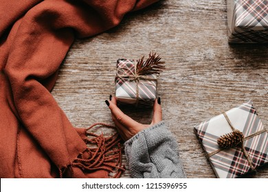 Christmas concept. Little present box in the woman hand beside brown scarf and presents on the wooden table. Top view