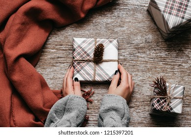 Christmas concept. Little present box in the woman hands beside brown scarf and presents on the wooden table. Top view