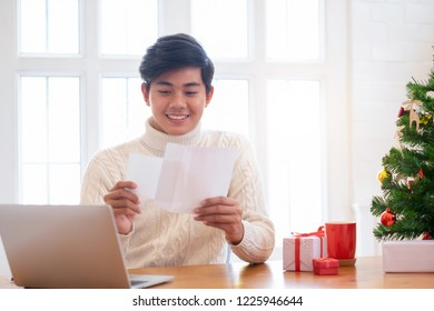 Christmas concept. Man wearing white sweater opening and sending christmas card.