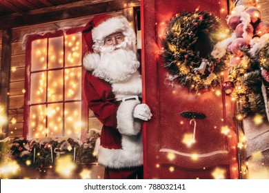 Christmas concept. Portrait of a fairytale Santa Claus looks out of the door of his house. Beautiful house decorated for Christmas. Time of miracles.