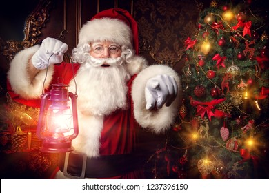 Christmas concept. Portrait of a magic Santa Claus which is standing with lantern and is seeing miracles. Beautiful home decorated for Christmas. Time of miracles.