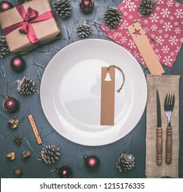 Christmas concept, postcard, gift box, Christmas toys and cones, on a grey background, lined around a white plate