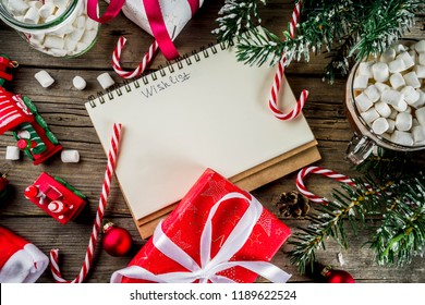 Christmas concept, preparation for xmas holidays, notepad for wish list, santa letter. to do list, with hot hot chocolate cup, Christmas tree decor, fir branches. Old wooden table copy space top view