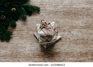 Christmas concept. Present boxes on the wooden background beside spruce branches. Top view